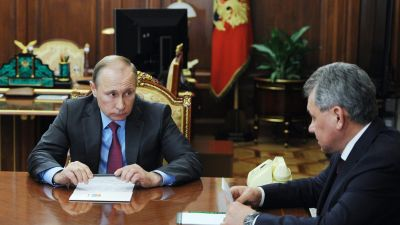 epa05211565 President of Russia Vladimir Putin (L) talks to Russian Defense Minister Sergey Shoygu during their meeting in the Kremlin, Moscow, Russia, 14 March 2014. Putin has ordered the withdrawal of Russian military troops from Syria, according to