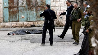 epa05228530 Israeli police gesture at the scene of a shooting next to a body of dead Palestinian in Tal Rumaida in the West Bank city of Hebron, 24 March 2016. Two Palestinians Ramzi Qasrawi and Abdelfattah Sharif were shot dead by Israeli troops after
