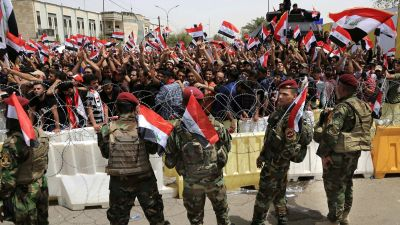 Iraqi security forces guard the heavily fortified Green Zone as followers of Iraq's influential Shiite cleric Muqtada al-Sadr wave national flags as they gather in front of the Green Zone, ahead of a scheduled parliament session to press for a vote