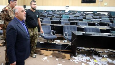 epa05285575 A handout picture released by Iraqi prime minister office shows Iraqi Prime Minister Haider al-Abadi (L) inspecting the damage caused by angry protesters after storming the Iraqi parliament building in Baghdad's fortified Green Zone,