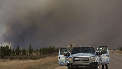 People stop to take photos of a wildfire south of Fort McMurray, Alberta, Canada on Thursday May 5, 2016. Raging wildfires in the Canadian province of Alberta have moved south, forcing three more communities to evacuate and an emergency operations center