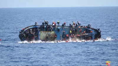 epa05328920 A handout picture released by the Italian Navy shows people jumping out of a boat right before it overturns in Canal of Sicily off the Libyan coast, 25 May 2016. The Italian navy says it has recovered five bodies from the overturned migrant