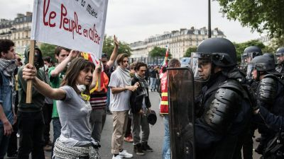 epa05330808 A woman holding a sign reading 'People are Angry' faces French riot police during a protest against the government's labour market reforms, at Place de la Nation, in Paris, France, 26 May 2016.  EPA/CHRISTOPHE PETIT TESSON
