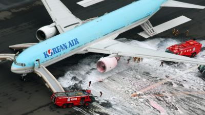 Firefighters gather near an engine of a Korean Air jet following an apparent engine fire on the tarmac at Haneda Airport in Tokyo Friday, May 27, 2016. All the passengers and crew were evacuated unharmed, Japanese media reported. (Kyodo News via AP) JAPA