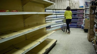 epa05155581 A woman shops in a supermarket in Caracas, Venezuela, 11 February 2016. Venezuelan Parliament has declared the 'National food crisis' and called the UN agencies FAO and Uniced to assess the risk of scarcity in the Venezuelan
