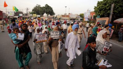 epa04482585 Sikhs hold posters as they take part in the 'Slavery Awareness March', organized by Sikh Youth Front on the occasion of 30th anniversary of Sikh genocide of November 1984 in Delhi and elsewhere, in Amritsar, India, 09 November 2014.