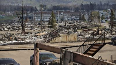 In this Friday, May 13, 2016 photo, the charred remains of various structures, buildings and vehicles litter the neighborhood of Abasand in wildfire-ravaged Fort McMurray, Alberta. More than 80,000 residents who fled Canada's main oil sands town because