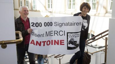 epa05289528 People holding a placard reading: '200,000 signatures say Thank you Antoine' arrive for another day of the so-called LuxLeaks Whistleblower trial, in Luxembourg, 04 May 2016. Three men, two former employees of accounting firm,
