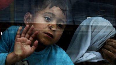 epaselect epa05254346 A boy looks out of a bus window as refugees from Syria and Iraq board a bus transferring them to a new organised hosting facility in Attica from the port of Piraeus, Greece, 11 April 2016, where almost 5,000 migrants and refugees