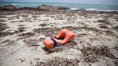 epa05343251 A buoyancy aid lies on a beach where bodies of migrants washed up, in Zuwarah, west of Tripoli, Libya, 02 June 2016. According to media reports citing Red Crescent officials, at least 85 bodies have washed up onto Libyan beaches this week.
