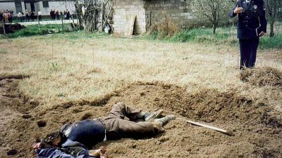 BEL05-200000404-NIS, SERBIA, YUGOSLAVIA: A policeman (R) on Tuesday, 04 April 2000, stands next to the body of Vladimir Jovanovic (72), who was killed by a cluster bomb which was dropped during the last year NATO bombing campaign on Yugoslavia and failed