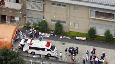 Ambulance crew and police officers  are seen outside a facility for the handicapped where a number of people were killed and dozens injured in a knife attack Tuesday, July 26, 2016,  in Sagamihara, outside Tokyo. (Kyodo News via AP)