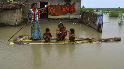 epa04365958 A man takes his family to a safer place as their house is submerged by flood waters in the flood affected Morigaon district of Assam state, India, 24 August 2014. According to media reports, nearly 50 people have died in India's flood-hit