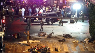 FILE - In this Aug. 17, 2015 file photo, a policeman photographs debris from an explosion in central Bangkok, Thailand. A Thai military court on Tuesday, Aug. 23, 2016 began the trial of two foreigners charged with the bombing of a popular shrine in