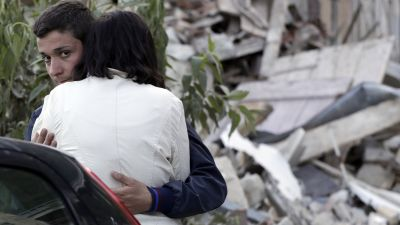 Two people hug each other next to the remains of a collapsed house following an earthquake in Pescara Del Tronto, Italy, Wednesday, Aug. 24, 2016. The magnitude 6 quake struck at 3:36 a.m. (0136 GMT) and was felt across a broad swath of central Italy,