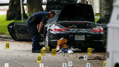 A police officer investigates a car belonging to local lawyer, Nathan Desai, who shot and injured multiple people before he was killed by police at Law Street at Weslayan in Houston, Monday, Sept. 26, 2016. (Michael Ciaglo/Houston Chronicle via AP)