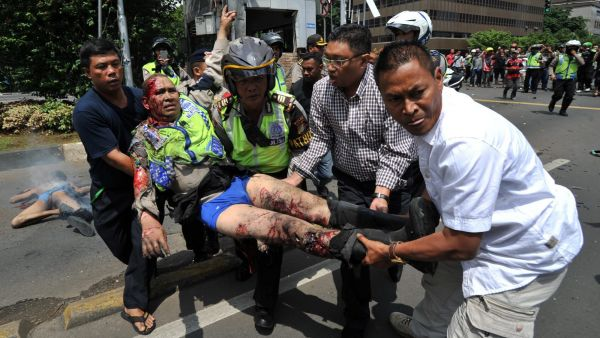 epa05100971 An injured Indonesian policeman is evacuate from the site of a bomb blast in front of a shopping mall in Jakarta, Indonesia, 14 January 2016. Explosions near a shopping centre in the Indonesian capital Jakarta killed at least three people on