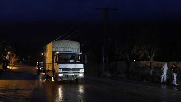 epa05102079 Trucks carrying aid material arrive at the entrance of the besieged town of Madaya, in the countryside of Damascus, Syria, 14 January 2016. Convoys of humanitarian supplies, the second in a week, were on their way to three besieged Syrian