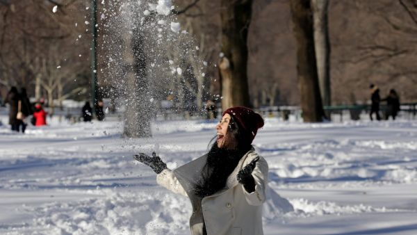 epa05123754 A woman enjoys the snow in Central Park in New York, New York, USA, 24 January 2016. The East Coast of the US is beginning to recover from a major blizzard that dumped near-record amounts of snow in the region.  EPA/PETER FOLEY