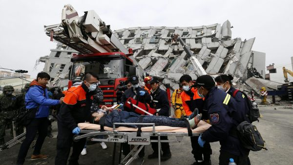 epa05145497 Rescuers carry a survivor from a collapsed building following a 6.4 magnitude earthquake that struck the area in Tainan City, Taiwan, 06 February 2016. At least three people, including an infant, were killed and dozens injured when a high-rise