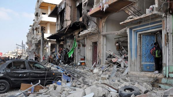 epa05173444 Damaged cars and buildings are seen near the site of a twin bomb attack in the city of Homs, Syria, 21 February 2015. The death toll from the double bomb attack in the Syrian city of Homs rose to 46, including at least 28 civilians, the Syrian