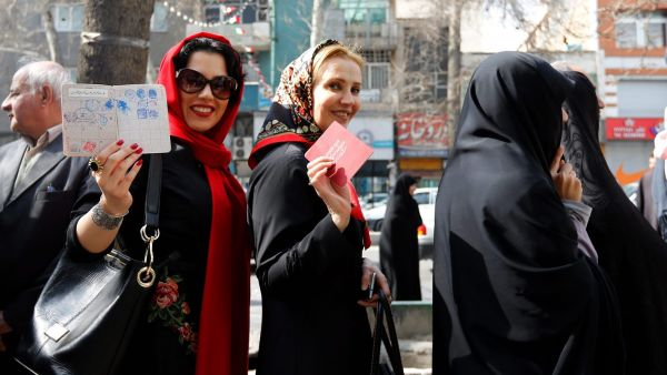 epaselect epa05181521 Iranian women show their IDs as they wait in line to cast their votes in the parliamentary and Experts Assembly election outside a polling station at Ershad Mosque in Tehran, Iran, 26 February 2016. Voting began in Iran's