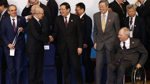 epa05183073 Chinese Finance Minister Lou Jiwei (front C) greets Turkish Deputy Prime Minister Mehmet Simsek (front L) as People's Bank of China Governor Zhou Xiaochuan (Front 2-R) and German Finance Minister Wolfgang Schaeuble (front R) look on