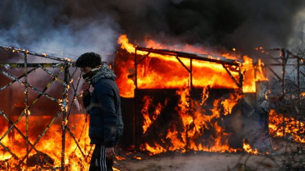 epaselect epa05187694 A refugee watches a shelter burn during the start of the expulsion of a part of the Jungle migrant camp in Calais, France, 29 February 2016.  A court in Lille, northern France, upheld an expulsion order issued by local authorities to
