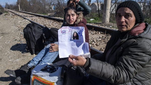 epa05195984 A refugee woman shows a stamped document for her family after they crossed the border between Greece and Macedonia, near Gevgelia, The Former Yugoslav Republic of Macedonia, 05 March 2016. Migration restrictions along the so-called Balkan