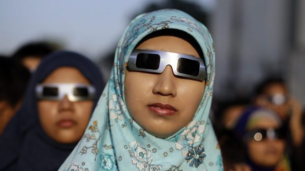 epa05202014 An Indonesian resident wearing eclipse glasses looks up at the sun during a solar eclipse outside the planetarium in Jakarta, Indonesia, 09 March 2016. A total solar eclipse plunged parts of the Indonesian archipelago into eerie day-time