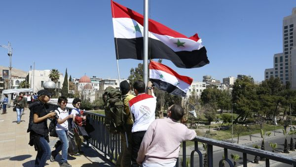 epa05206487 Syrians raise the national flag at a main bridge in the old city of Damascus, Syria, 11 March 2016.The Syrian Ministry of Tourism launched an event to raise the Syrian flags on the markets and the masts of a main bridge in Damascus and on the