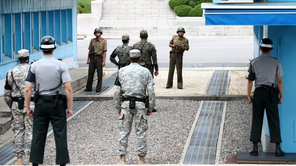 epa04862317 North Korean soldiers (background) look towards South Korea as South Korean soldiers stand guard at the Military Demarcation Line in the Demilitarized Zone (DMZ) in the border village Panmunjom, South Korea, 27 July 2015. Both Koreas