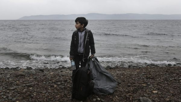 epa04973314 A boy carries his belongings upon his arrival on the island of Lesvos after having crossed the Aegean Sea from Turkey in a rubber dinghy, Lesvos island, Greece, 11 October 2015. A recently agreed European Union plan to relocate tens of