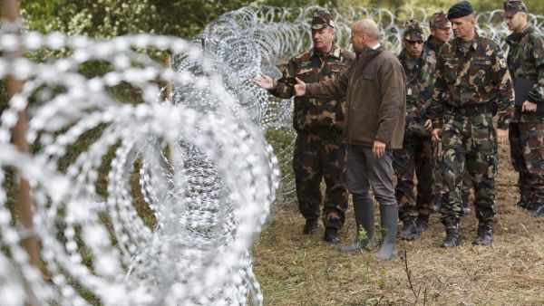 epa04957460 Hungarian Defence Minister Istvan Simicsko (2-L) and Chief of Staff of the Hungarian Defence Forces Colonel-general Tibor Benko (L) are inspect the temporary fence installed at the border between Hungary and Croatia near Zakany, Hungary, 30