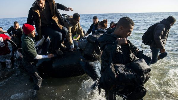 epa05057071 Migrants, who came from Turkey, make landfall from their overloaded rubber dinghy as they arrive at the coast near Mytilene, Lesbos island, Greece, 06 December 2015. France and Germany are calling for the deployment of EU border agents to