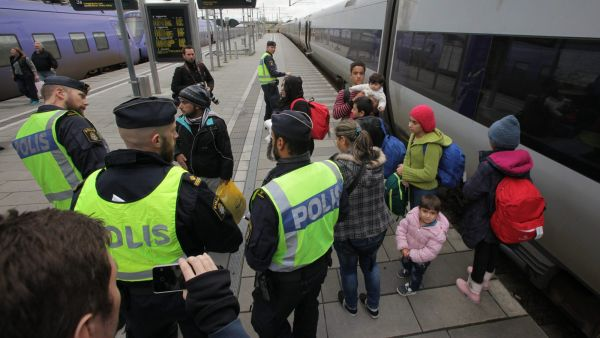 epa05021902 Swedish police gather a group of migrants off an incoming train at the Swedish end of the bridge between Sweden and Denmark, Malmo, Sweden, 12 November 2015. Sweden has announced the introduction of temporary border checks to control the flow