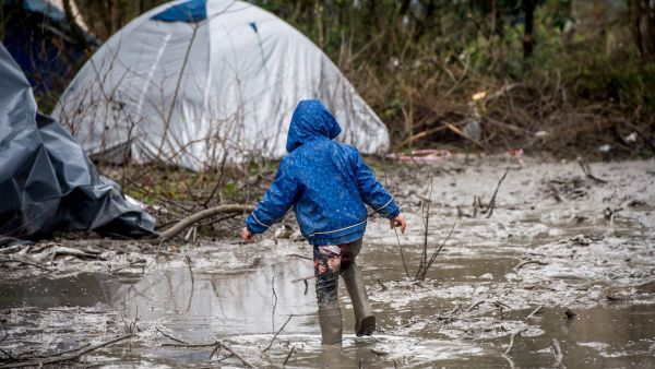epa05095668 A refugee child walks in the mud in refugee camp in the coastal town of Grande-Synthe near Dunkirk, northern France, 10 January 2016. Despite most of the attention is on the so-called 'Jungle' in near-by Calais, the refugee camp in