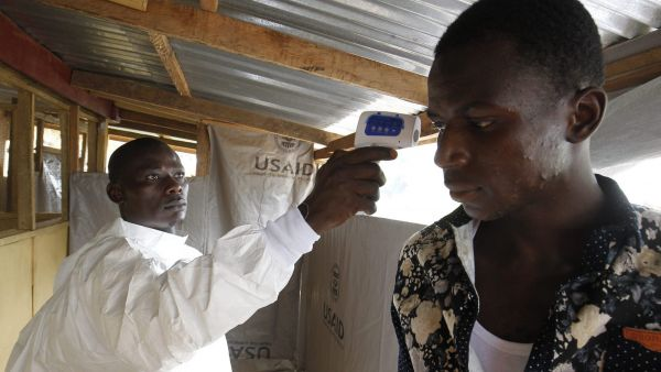 epa05057926 YEARENDER 2015 NOVEMBERA Liberian nurse tests the temperature of a man before entering a hospital in Monrovia, Liberia, 26 November 2015.  EPA/AHMED JALLANZO