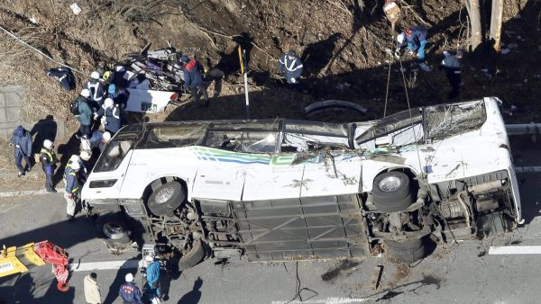 Investigators work near a damaged bus after it was transferred by crane onto a road in Karuizawa, Nagano prefecture, central Japan Friday, Jan. 15, 2016. The overnight tour bus on its way to a ski resort careened off a mountain road early Friday, killing