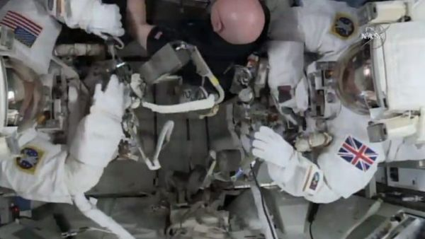 This photo taken from video provided by NASA shows astronaut Scott Kelly, center, help gather equipment for U.S. astronaut Tim Kopra, left, and British astronaut Tim Peake, as they prepare for a space walk at the International Space Station on Friday, Jan