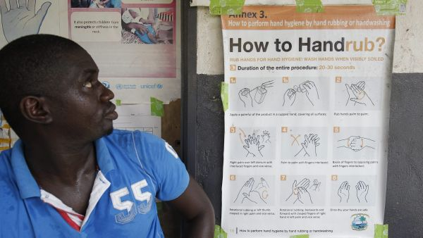epa05043361 A Liberian man reads an ebola preventive message on a bulletin at a hospital in Monrovia, Liberia, 26 November 2015. Three new cases of Ebola were confirmed in Liberia last week less than three months after the country was declared free of the