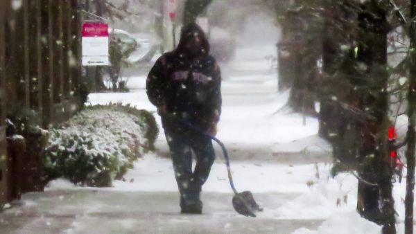 epa05036433 A man shovels snow off a sidewalk in temperatures around 35 degrees (1.6 C) in Wilmette, Illinois, USA, 21 November 2015. After a mild Autumn, the Midwest US is experiencing its first taste of winter weather as Winter Storm Bella moves to the