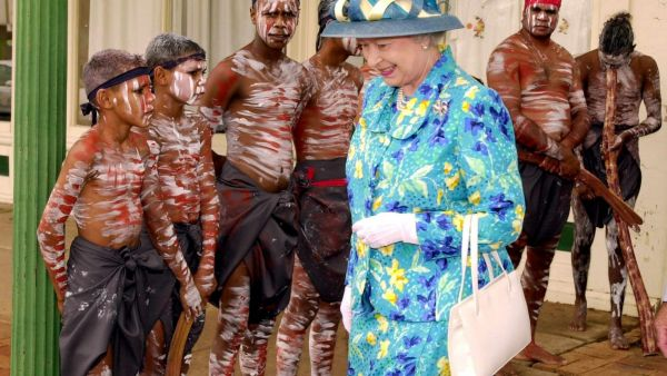 Queen Elizabeth II walks past the Ngemba Muranari dancers at the Muda Aboriginal Language and Cultural Centre in Bourke, 900 kilometers north west of Sydney, Australia 22 March 2000. The Queen is on a two week tour of Australia, her first since 1992.
