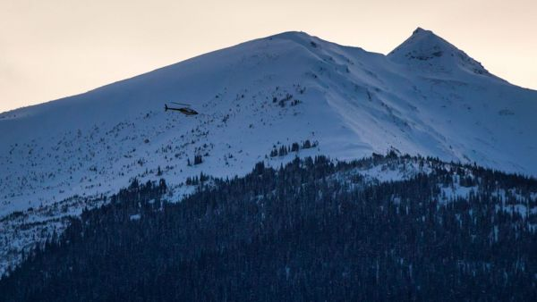 A helicopter flies past a snow-capped mountain top near McBride, British Columbia on Saturday, Jan. 30, 2016. Five snowmobilers died Friday in a major avalanche in the Renshaw area east of McBride. (Darryl Dyck/The Canadian Press via AP)