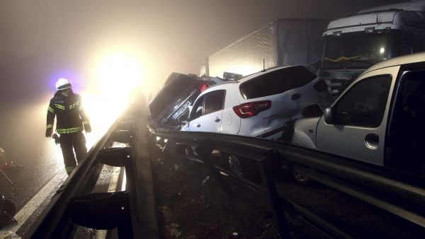 A fireman walks past a pileup on a motorway in Senozece, Slovenia, Saturday, Jan. 30, 2016. A massive pileup involving dozens of cars and trucks in dense fog killed four people on Saturday and injured 30 on a highway in western Slovenia. (AP Photo/Zdravko