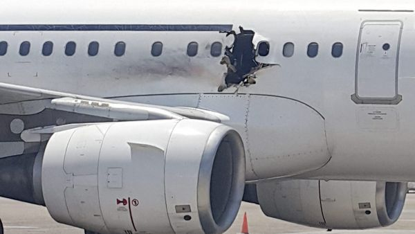 In this Tuesday, Feb. 2, 2016 photo, a hole is photographed in a plane operated by Daallo Airlines as it sits on the runway of the airport in Mogadishu, Somalia. A gaping hole in the commercial airliner forced it to make an emergency landing at Mogadishu&