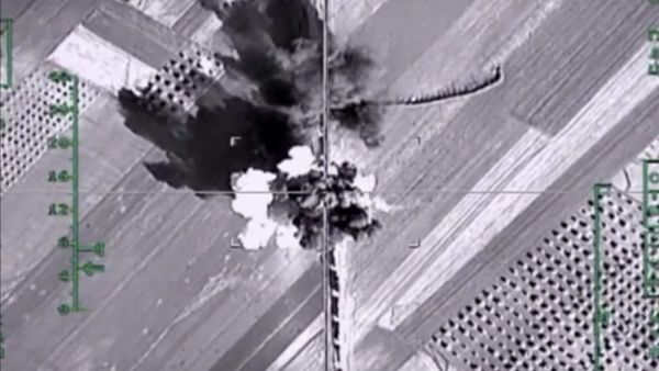 In this photo made from the footage taken from Russian Defense Ministry official web site on Monday, Feb.  1, 2016,  an aerial image shows what it says is a column of heavy trucks carrying ammunition hit by a Russian air strike near Aleppo, Syria. The