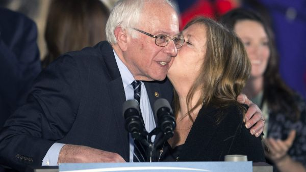 epa05152093 US Senator and Democratic Presidential hopeful Bernie Sanders (L) gets a kiss from his wife Jane (R) following his victory speech to supporters at Concord High School in Concord, New Hampshire, USA, 09 February 2016. Billionaire businessman