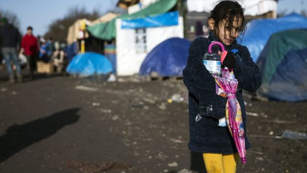 epa05104955 A young Kurdish girl walks along the muddy road framed with tents and shacks in the makeshift migrant camp in Grande-Synthe near Dunkirk, or Dunkerque, France, 16 January 2016. Despite most of the attention is on the so-called 'Jungle&