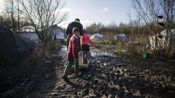 epa05104951 A Kurdish family walks on a bridge of fortune made of pallets put over pools of mud in the makeshift migrant camp in Grande-Synthe near Dunkirk, or Dunkerque, France, 16 January 2016. Despite most of the attention is on the so-called &#039